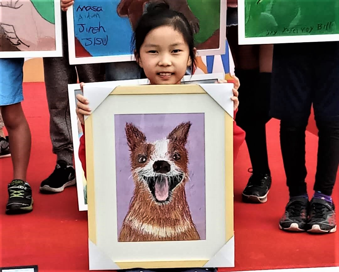 Child displaying her happy dog painting to raise awareness about rabies in China.