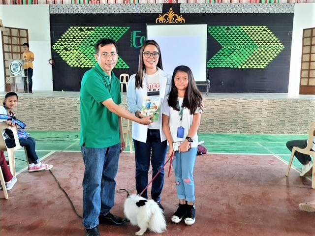 Educators and girl with dog learning about rabies prevention  and pet care, Philippines.